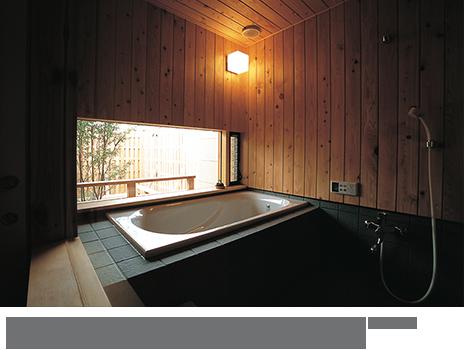 自然素材でつくり上げた心地よい浴室。風呂庭を眺めながらゆったりと入浴が楽しめる。(設計/大野正博)