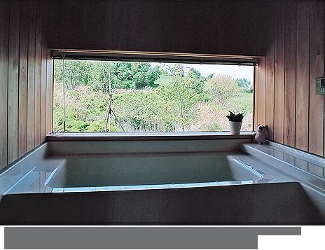 自然を眺めながらの入浴は格別。ハーフユニットバスを用い、腰から上は板張りとしている。(設計/大野正博)