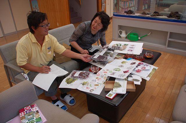 アーティスト・野田三千代さんの海藻おしばの作品を並べて打ち合わせ中の白井さんと池森さん