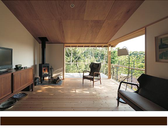 薪ストーブが設置された2階リビング。建具を壁に引き込んでしまえば森の中に浮かんでいるような感覚が味わえる。