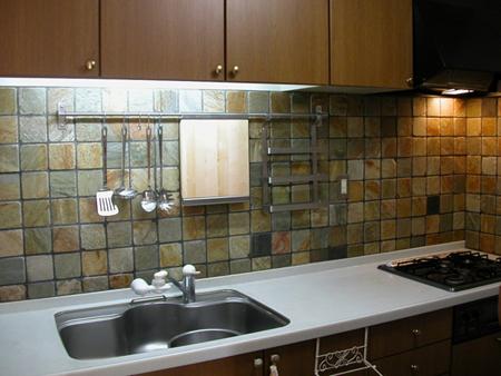 床用の天然石をキッチンの壁に張ったもの