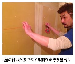 墨の付いた糸でタイル割りを行う墨出し
